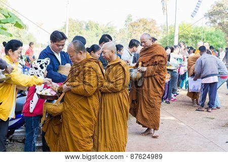 People Put Food On Buddhist Monk Alms Bowl