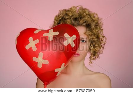Upset Woman With Ball In Shape Of Heart