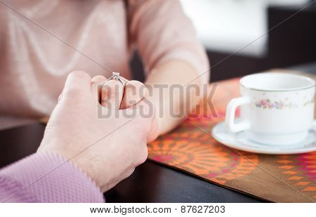 Couple holding their hands while having coffee