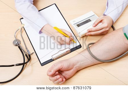 Nurse Measures Blood Pressure Of Patient