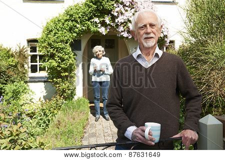 Senior Couple Standing In Cottage Garden Holding Coffee Cup