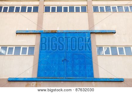 Industrial Wall With Blue Closed Metal Gate