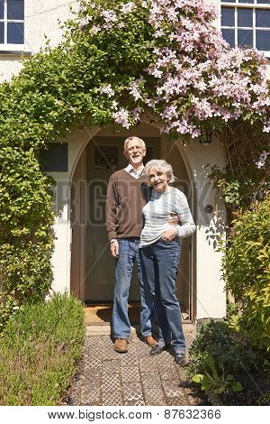 Retired Couple Standing Outside Pretty Cottage
