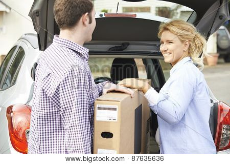 Couple Unloading New Television From Car Trunk