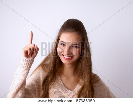 Portrait of a smiling young woman pointing up, standing