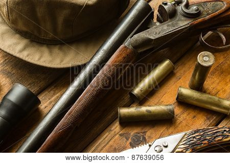 Hunting Rifle, Ammunition, A Knife And A Cap On The Table