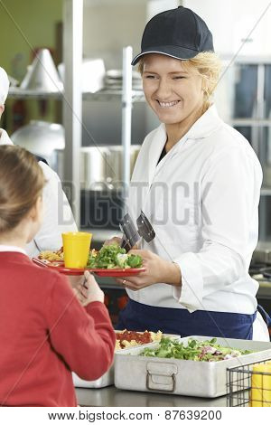 Famale Pupil In School Cafeteria Being Served Lunch By Dinner Lady