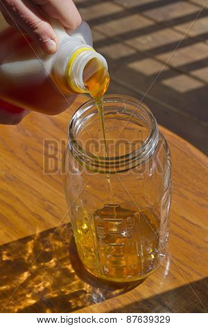 Close Up Of Hands Pouring Thick Honey Into A Glass Jar