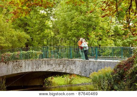 Mature couple leaning on railing of bridge resting during stroll in park