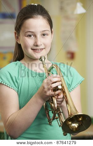 Girl Learning To Play Trumpet In School Music Lesson