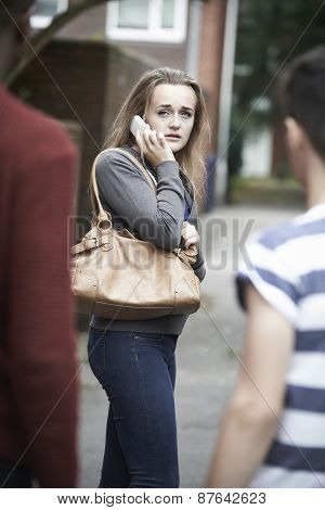 Teenage Girl On Mobile Phone Feeling Intimidated As She Walks Home