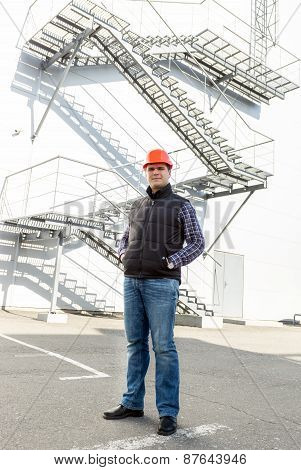 Confident Male Worker Posing Against Factory