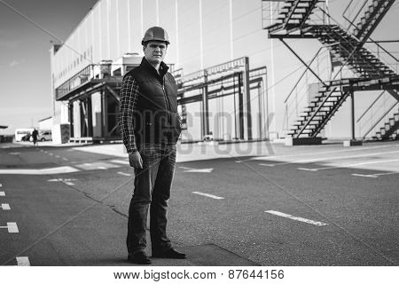 Black And White Photo Of Engineer Standing On Building Site