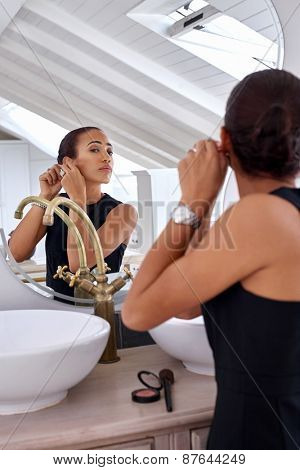 young professional business women with jewellery earings watch early morning at home bathroom
