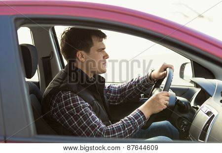 Young Concentrated Man Driving A Car