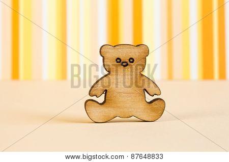 Wooden Icon Of Teddy Bear On Orange Striped Background
