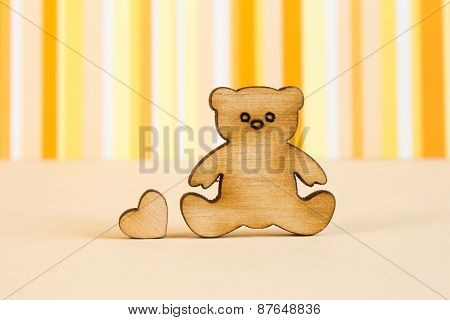 Wooden Icon Of Teddy Bear With Little Heart On Orange Striped Background