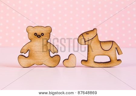 Wooden Icons Of Teddy Bear And Children's Rocking Horse With Little Heart On Pink Background