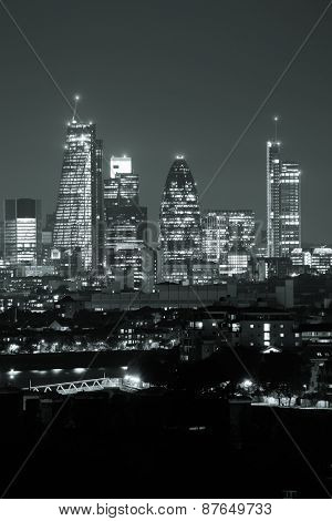 London cityscape with urban buildings over Thames River at night