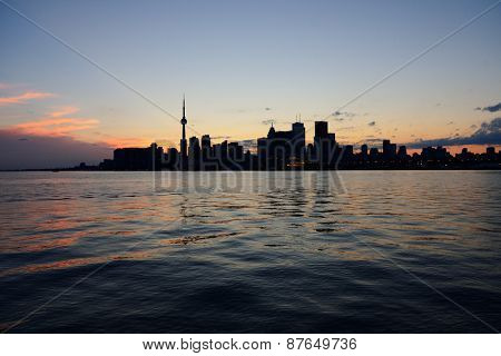 Toronto city skyline silhouette at sunset over lake with urban skyscrapers.