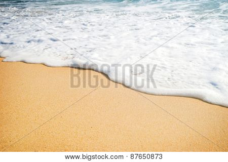 Close-up of a water edge and sand. Summer beach background with a blank space for any text.