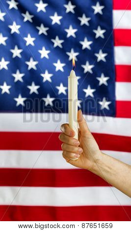 Hand Holding Lit Candle With Blurred Out Usa Flag In Background