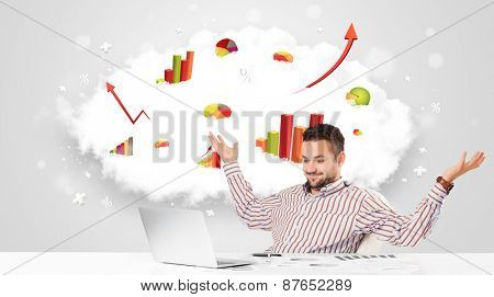 Handsome young businessman with cloud in the background containing colorful graphs and diagrams
