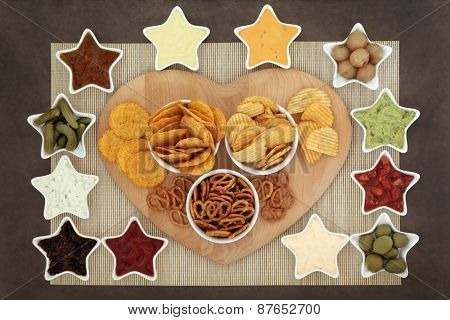 Savoury snack and dip food selection in star shaped  porcelain dishes on a wooden board over bamboo.