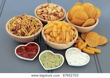 Savoury snack and dip food selection in wooden bowls and porcelain dishes.