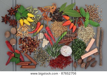 Herb and spice ingredients on a grey wooden background.