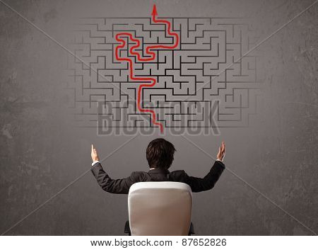Business man looking at a maze and the way out on brown wall