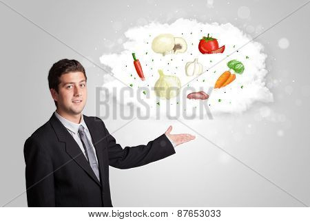 Handsome man presenting a cloud of healthy nutritional vegetables concept