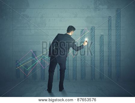 Young businessman drawing chart on wall