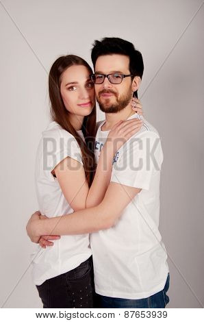 Young Couple Embracing And Looking At The Camera