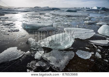 Glacier ice lagoon in Jokullsarlon, Iceland. The glacier breaks up into ice blocks in the lagoon before flowing out to sea as icebergs.
