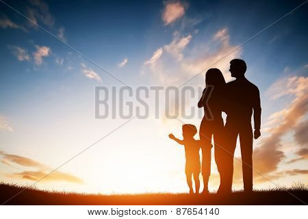 Happy family together, parents with their little child at sunset. Boy reaching the sun