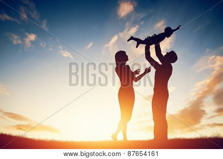 Happy family together, folks with their little tyke at nightfall. Father bringing child up noticeabl