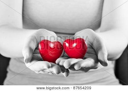 Two hearts in woman hands. Love giving, care, health, protection concept. Black and white.