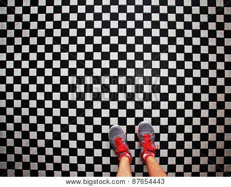 an overhead photo of a pair of tennis shoes on a grungy dirty checkered tile floor