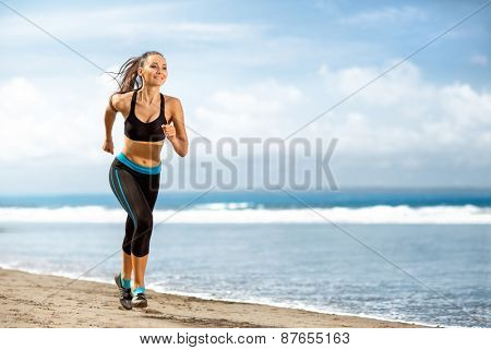 Jogging athlete woman running at sunny beach. Fitness runner girl training outside by the ocean sea in full body length in summer