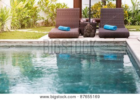 Clear blue water in swimming pool and sunbeds, tropical resort
