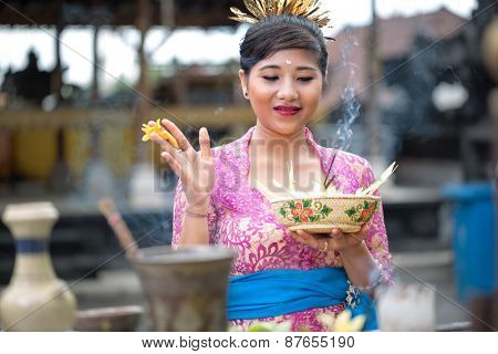 Young Balinese woman praying in Hindu temple
