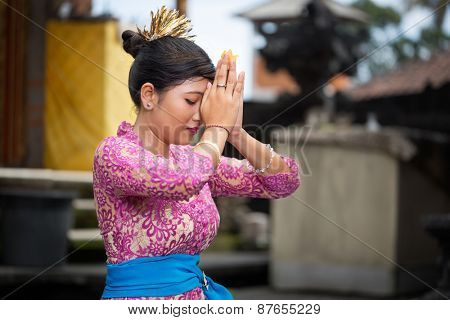 Balinese girl praying, she kneeling with joined hands in front of his head