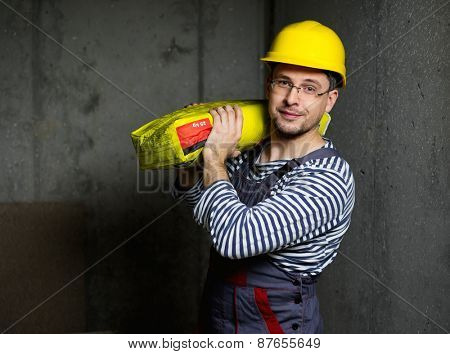 Builder carry bag with cement on his shoulder