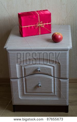 Red Gift and apple on the nightstand.