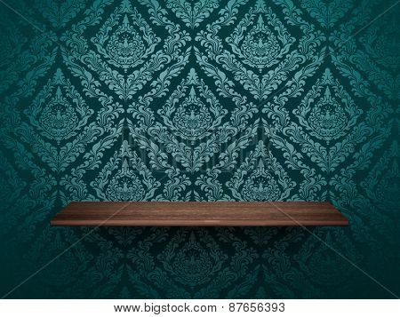 wooden shelf on wall with elegant wallpaper.