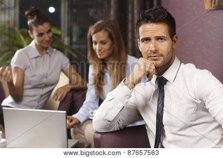 Portrait of young businessman in trouble, colleagues working at background.