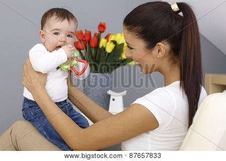 Young mother playing with baby boy, holding him on lap, smiling happy. Baby holding toy.