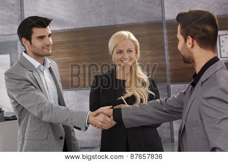 Businessmen shaking hands, businesswoman smiling with satisfaction.