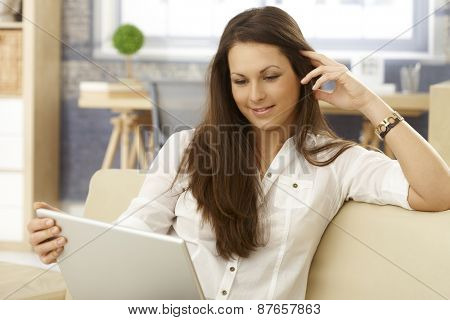 Young woman sitting on sofa at home, using laptop computer, smiling.
